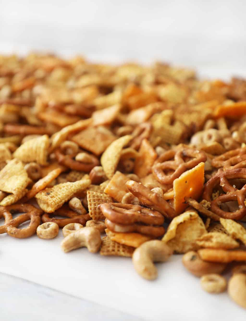 homemade Chex mix laid out on parchment paper to cool