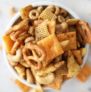 overhead view of homemade Chex mix in a small white bowl overflowing