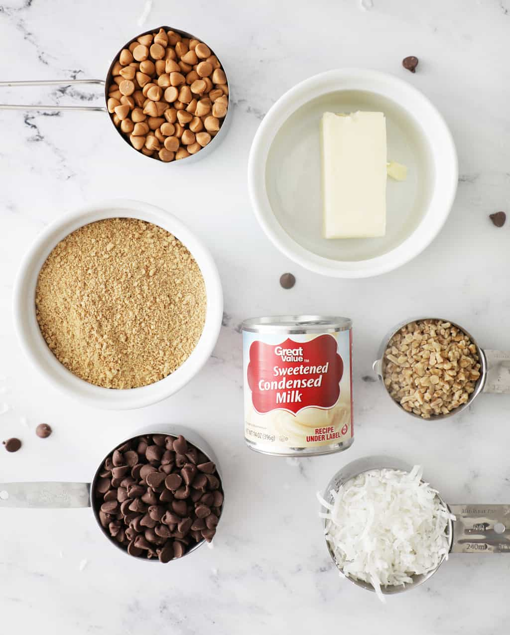 the ingredients to make seven layer bars on a white marble countertop