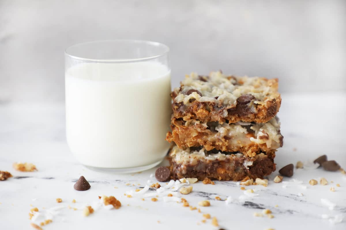 a glass of milk on a white marble counter next to a stack of magic cookie bars