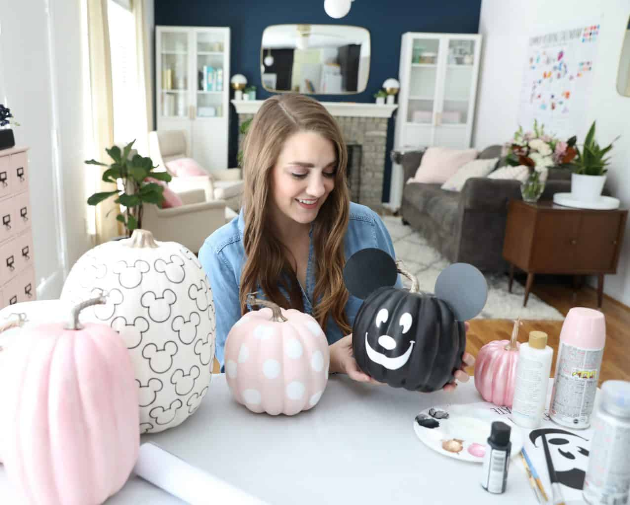 Woman holding mickey mouse pumpkin with craft supplies on table