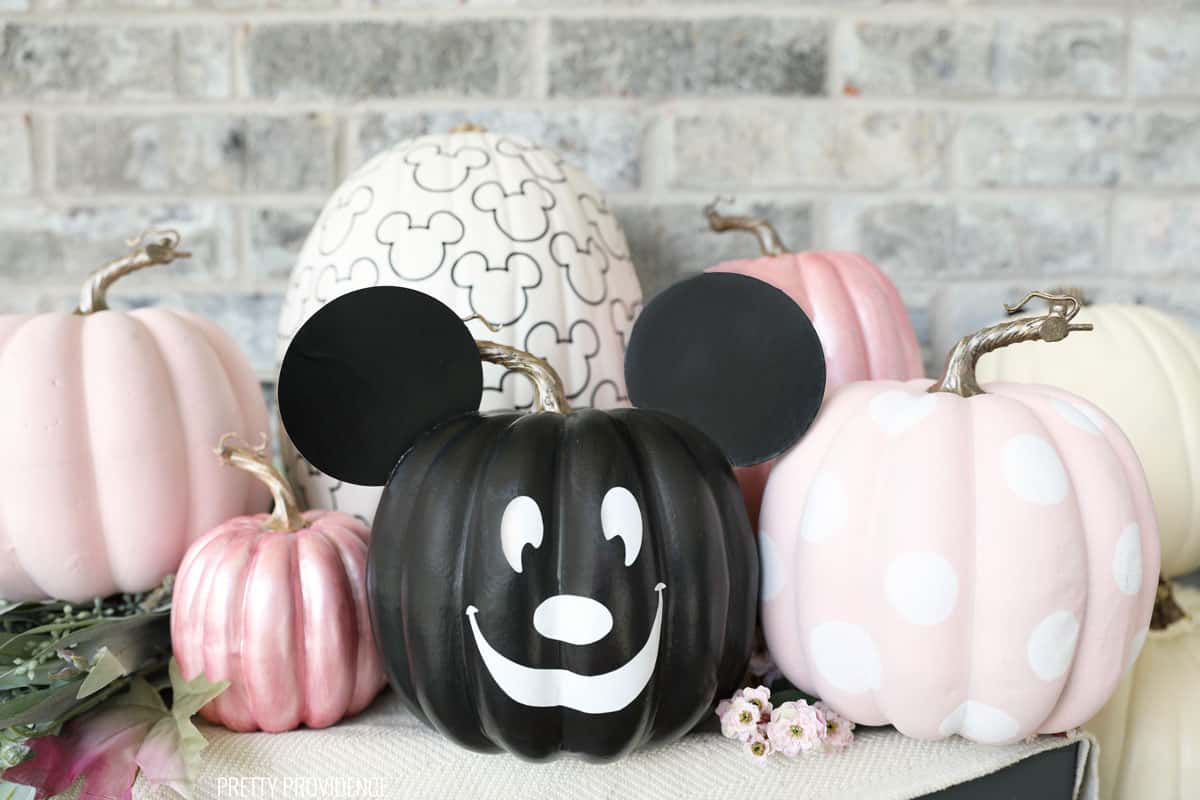 No-carve Mickey Mouse pumpkins on a porch, black pumpkin with Mickey ears, pink polka dot and patterned.