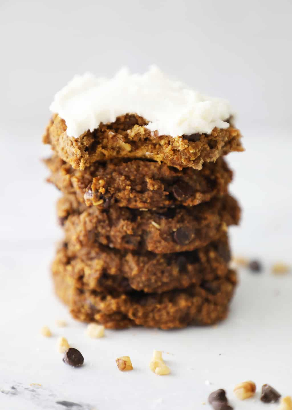 stack of five soft pumpkin cookies with cream cheese frosting on the top one