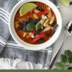 a bowl of tortilla soup in a white bowl on a black tea towel optimized for pinterest