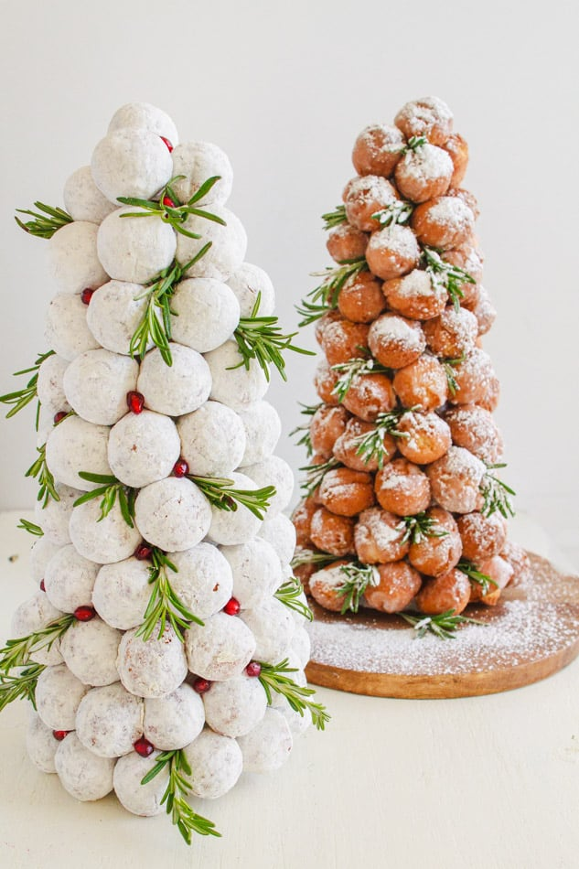 Donut holes in the shape of Christmas trees powdered sugar dust and sprigs of green