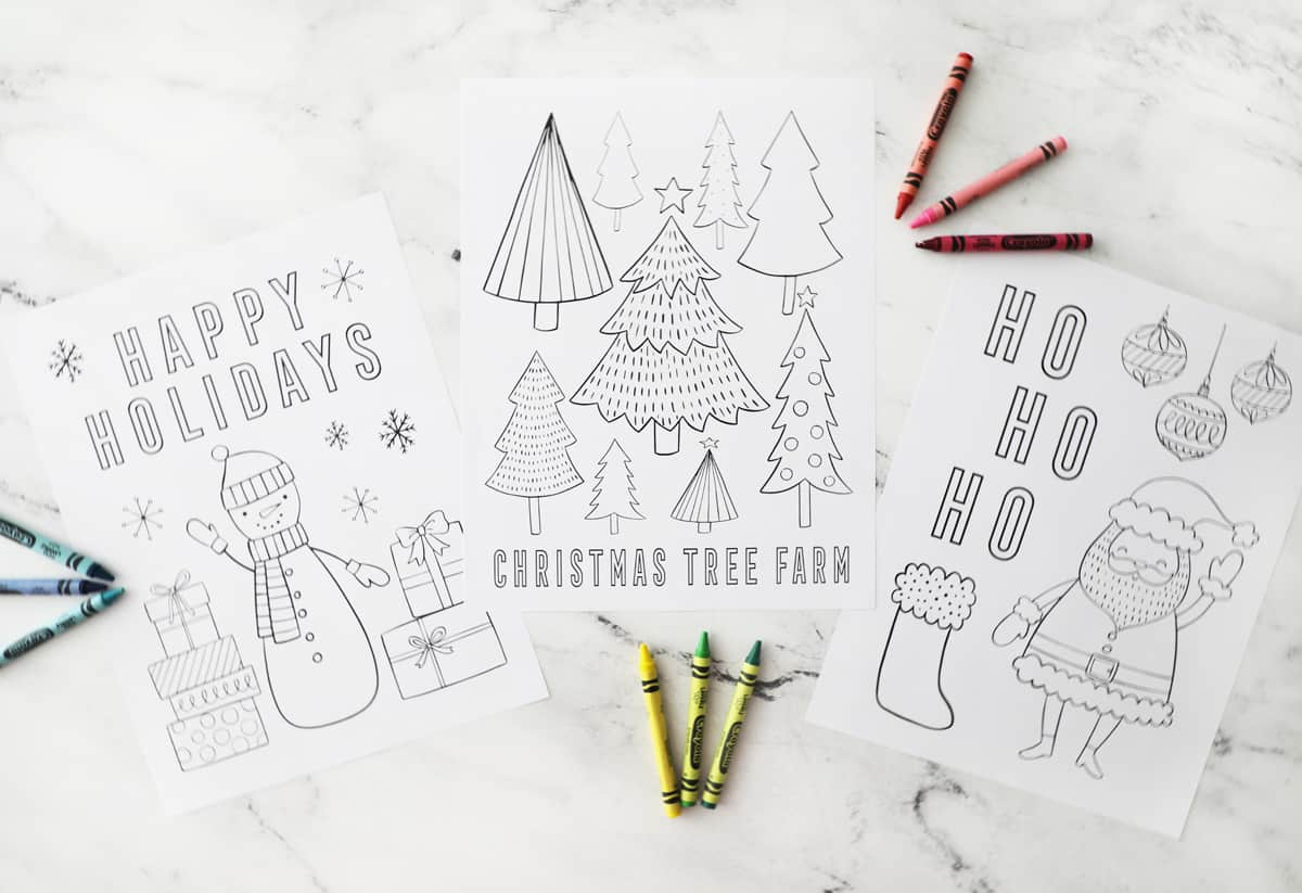 three printable Christmas coloring pages with crayons on a granite counter