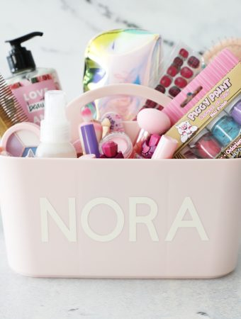 a pink makeup caddy with a name personalized on it filled with supplies