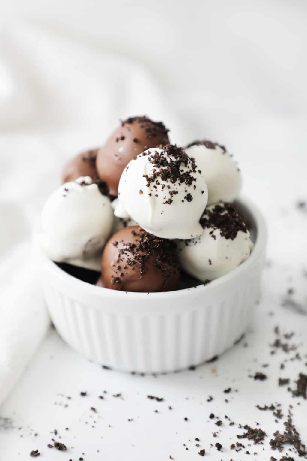 a white bowl overflowing with Oreo truffles next to a white linen napkin and some crumbs