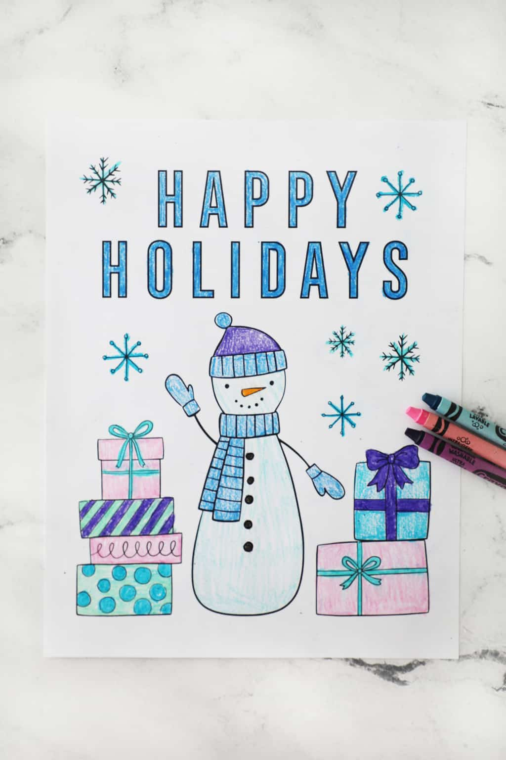 a snowman coloring page that says happy holidays next to some crayons