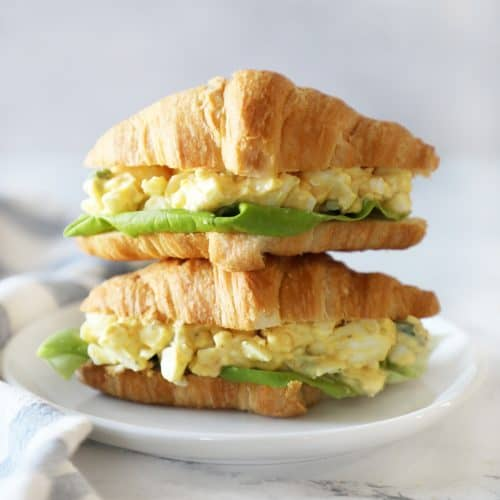 Two egg salad sandwiches stacked on a small white plate