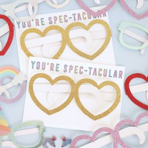 Kids valentines cards printable that say 'you're spectacular' with paper heart glasses taped onto them
