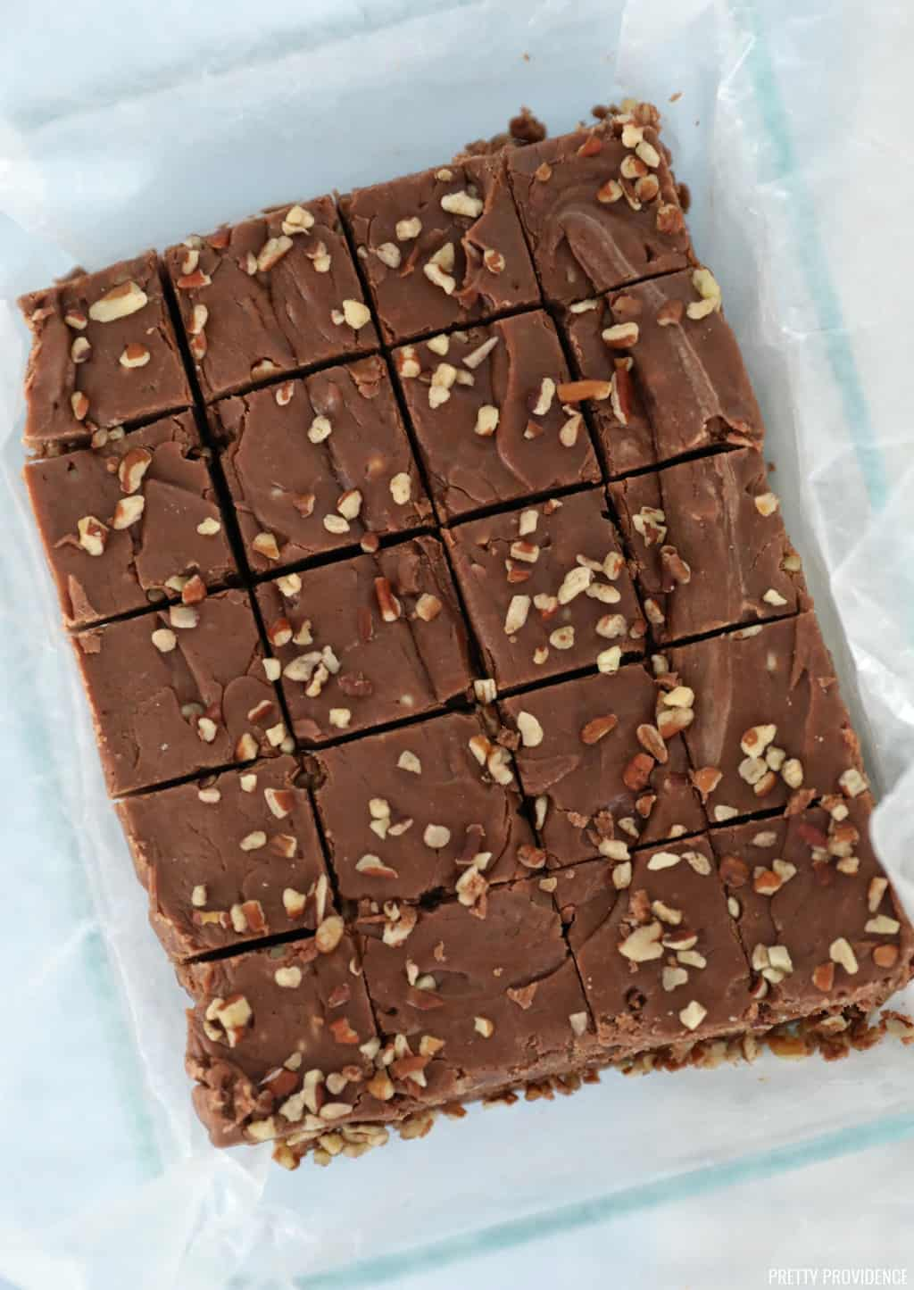 Homemade fudge with nuts on top cut into squares on wax paper