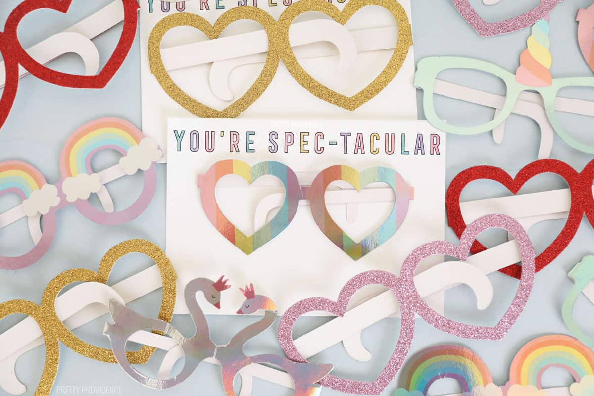 Valentines Heart glasses surrounding a white kids Valentine card that says 'you're spectacular'