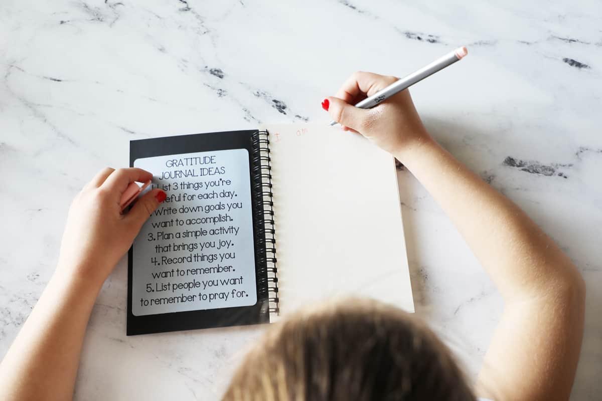 young girl writing in a kids gratitude journal birds eye view
