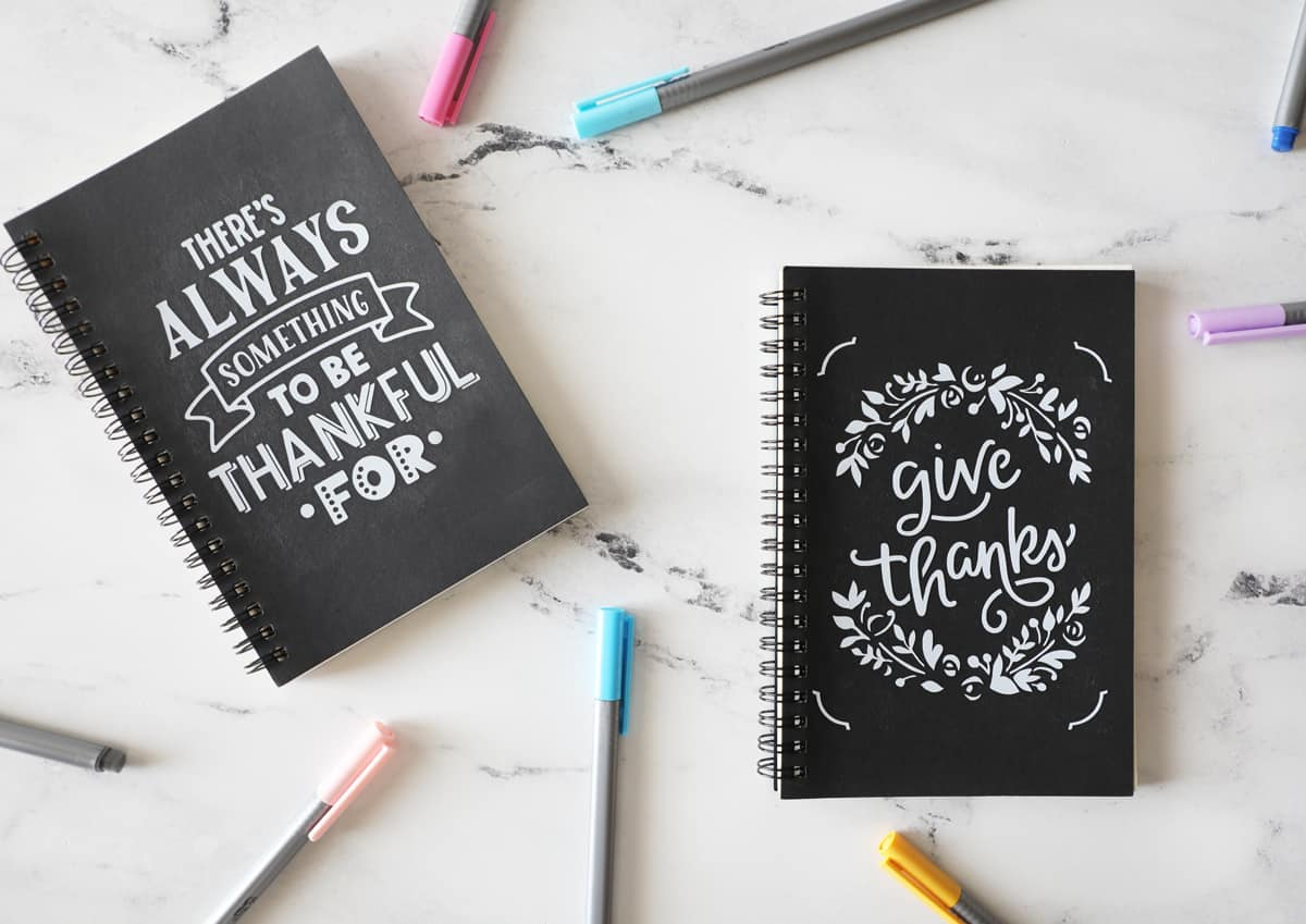 two gratitude journals on the marble countertop with colorful pens