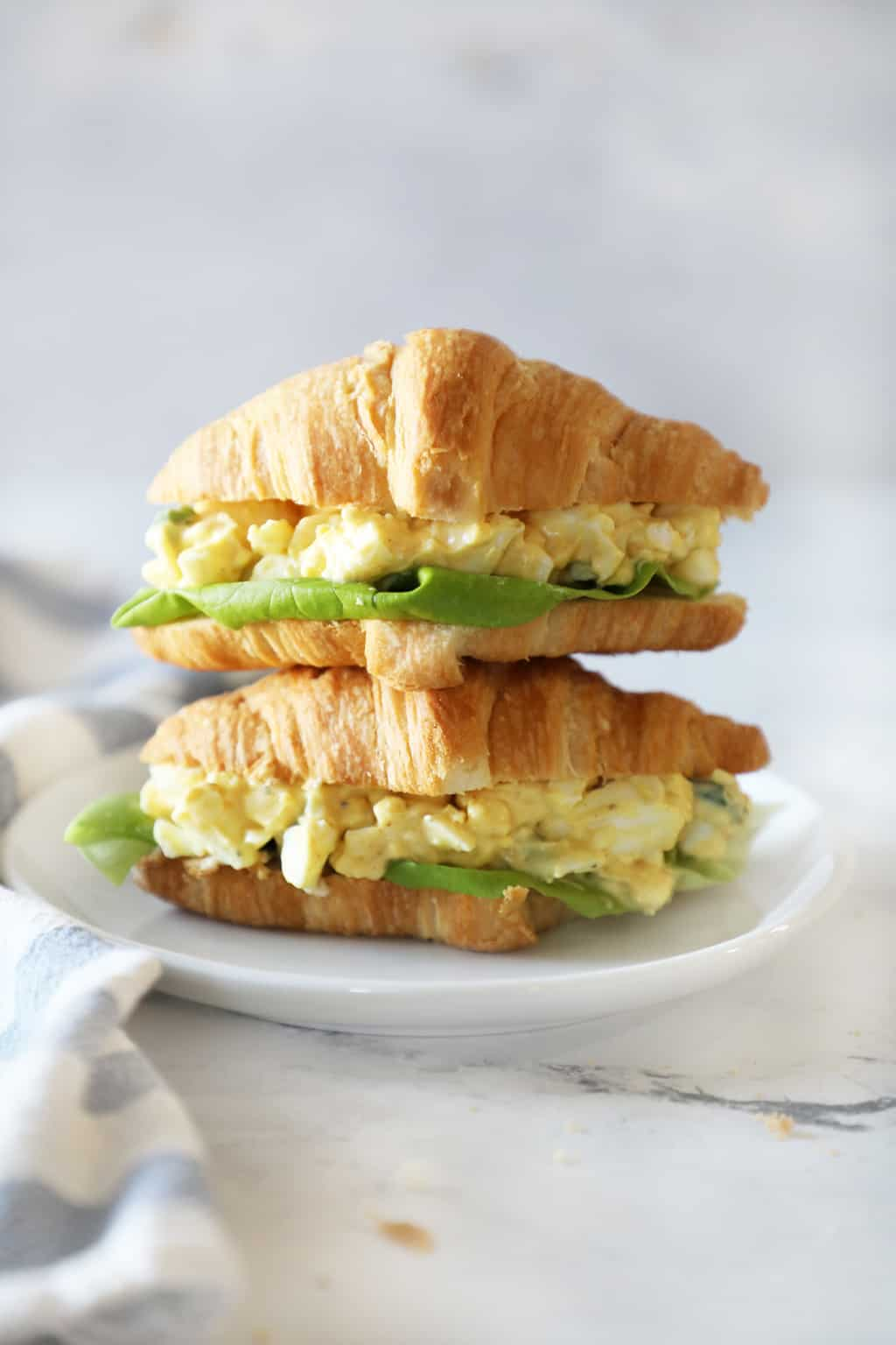 two croissant sandwiches on a white plate on a granite countertop