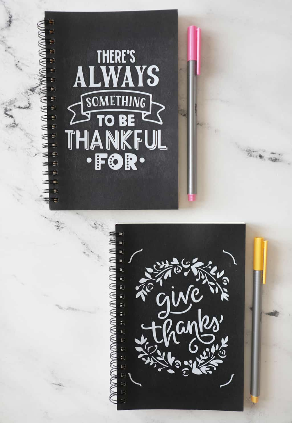 two gratitude journals on a marble countertop next to pens