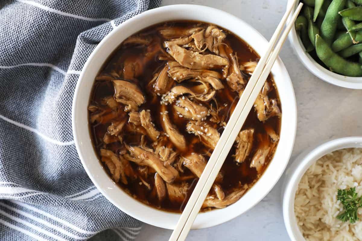 teriyaki chicken shredded in sauce in a white bowl