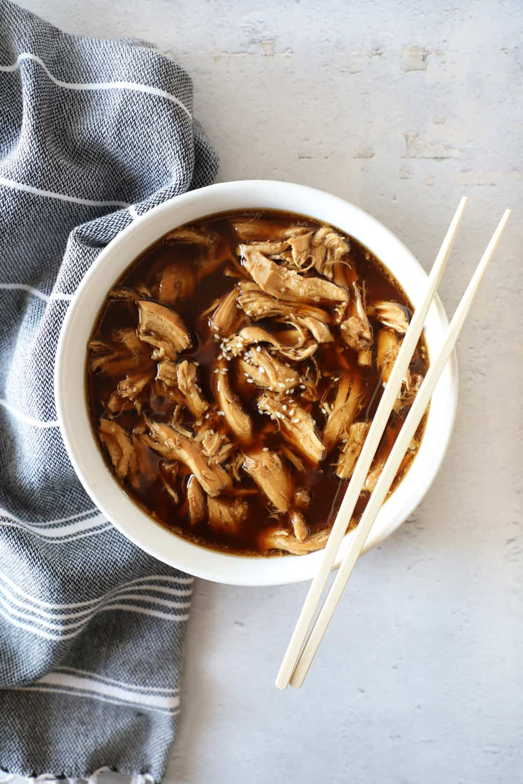 teriyaki chicken in a white bowl next to a grey tea towel and chopsticks