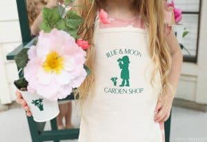 little girl holding flowers and wearing an apron with flowers and garden shop logo on it
