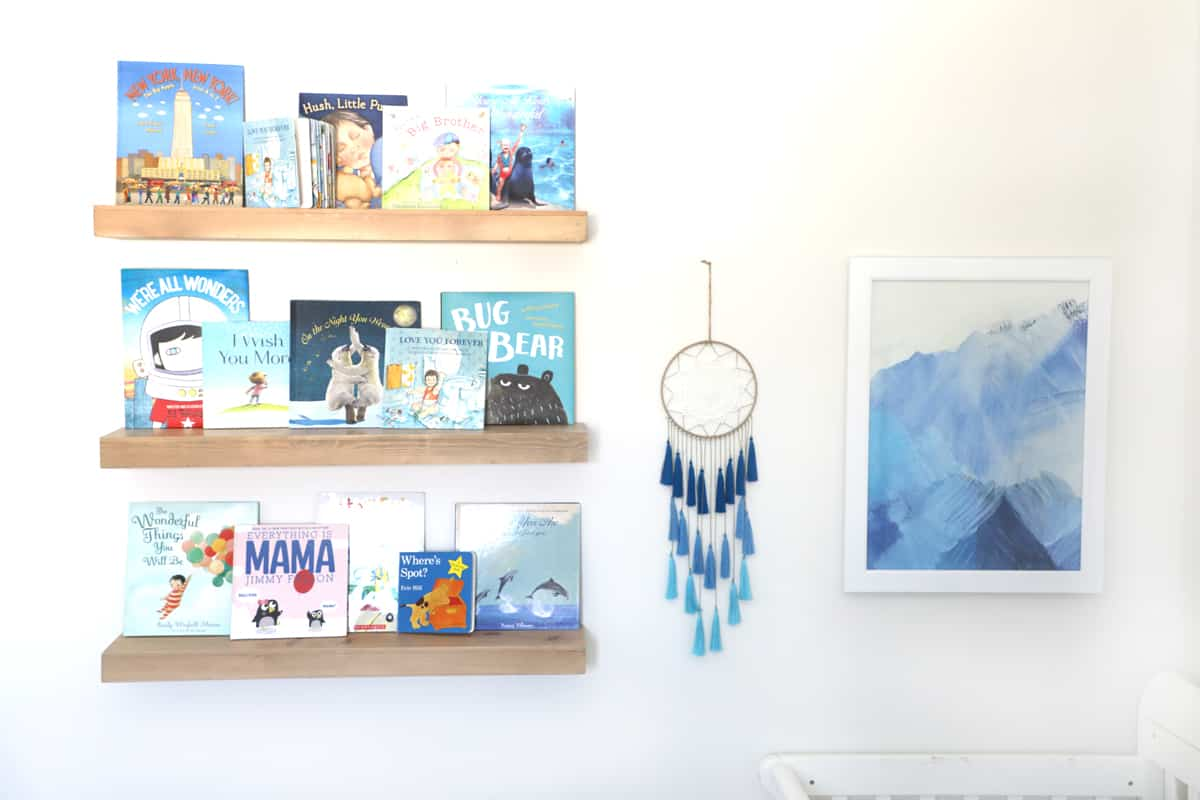 hanging shelves with blue books next to a dream catcher and a painting of blue mountains