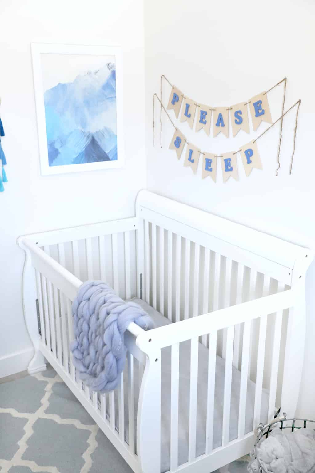 white crib by blue mountain painting with crochet blanket