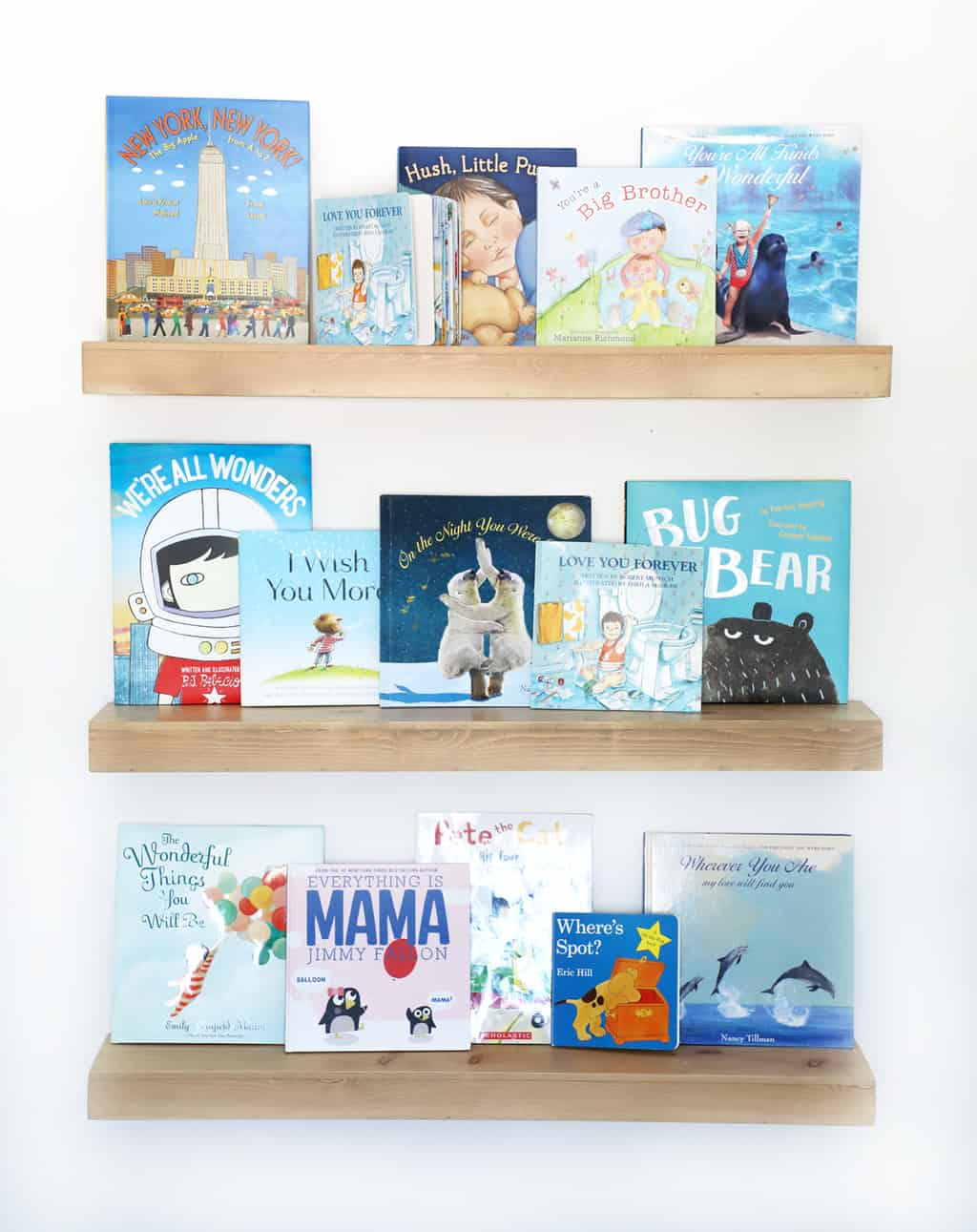 natural wood floating shelves with blue children's books on them
