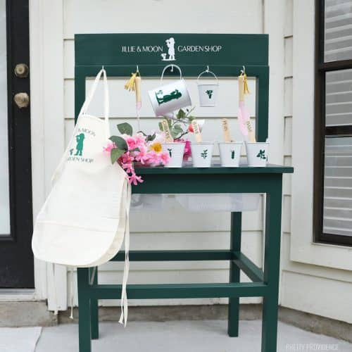 Green water and sensory table with aprons, watering cans and a garden themed sign