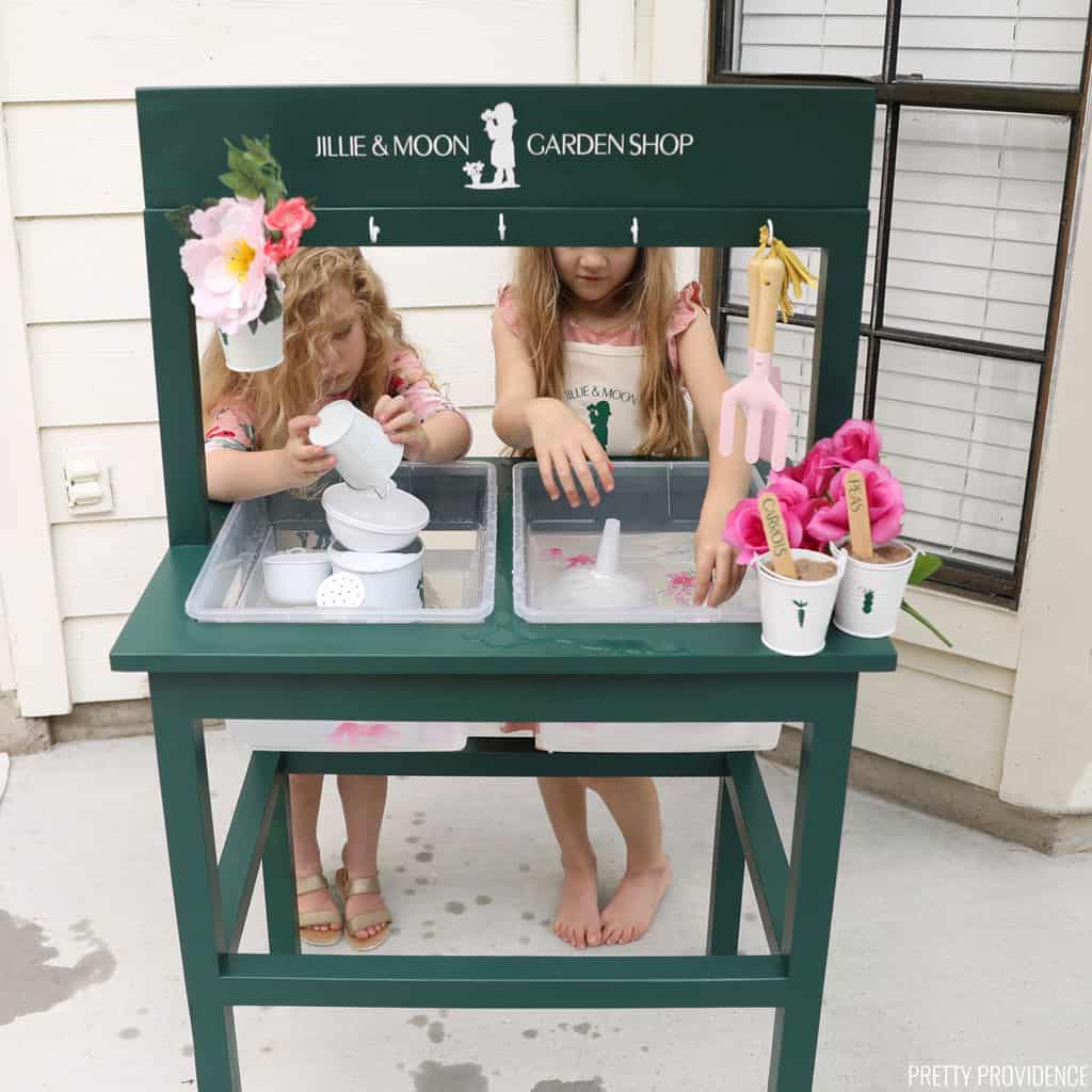 Two little kids playing with water at a DIY water table
