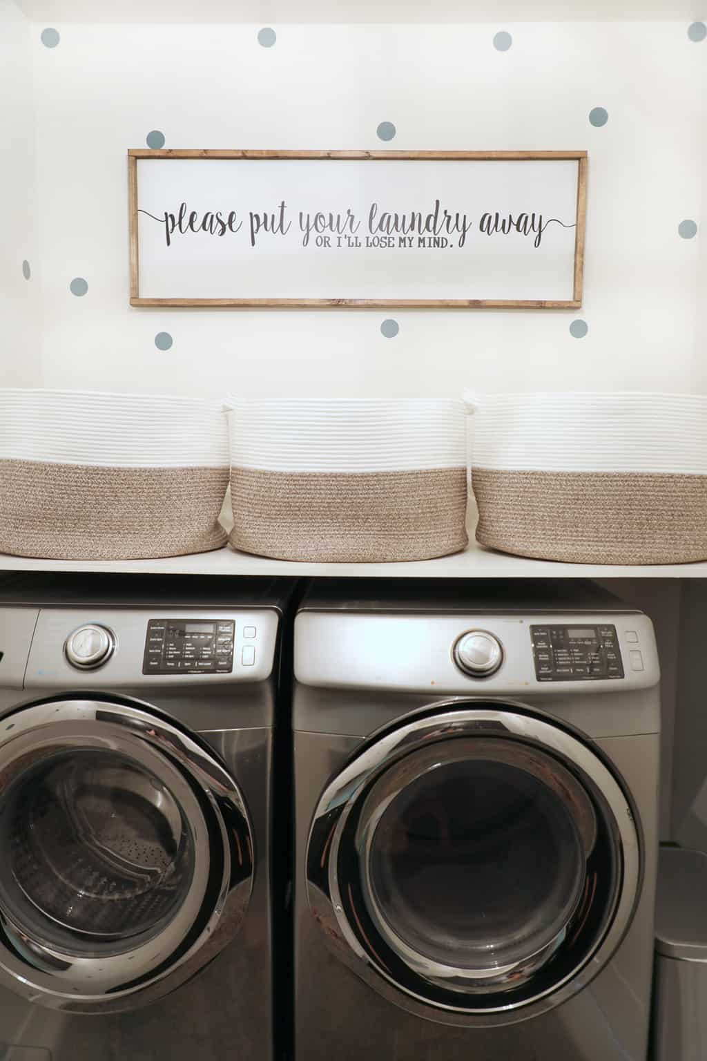funny laundry room sign over baskets on shelf and washer dryer