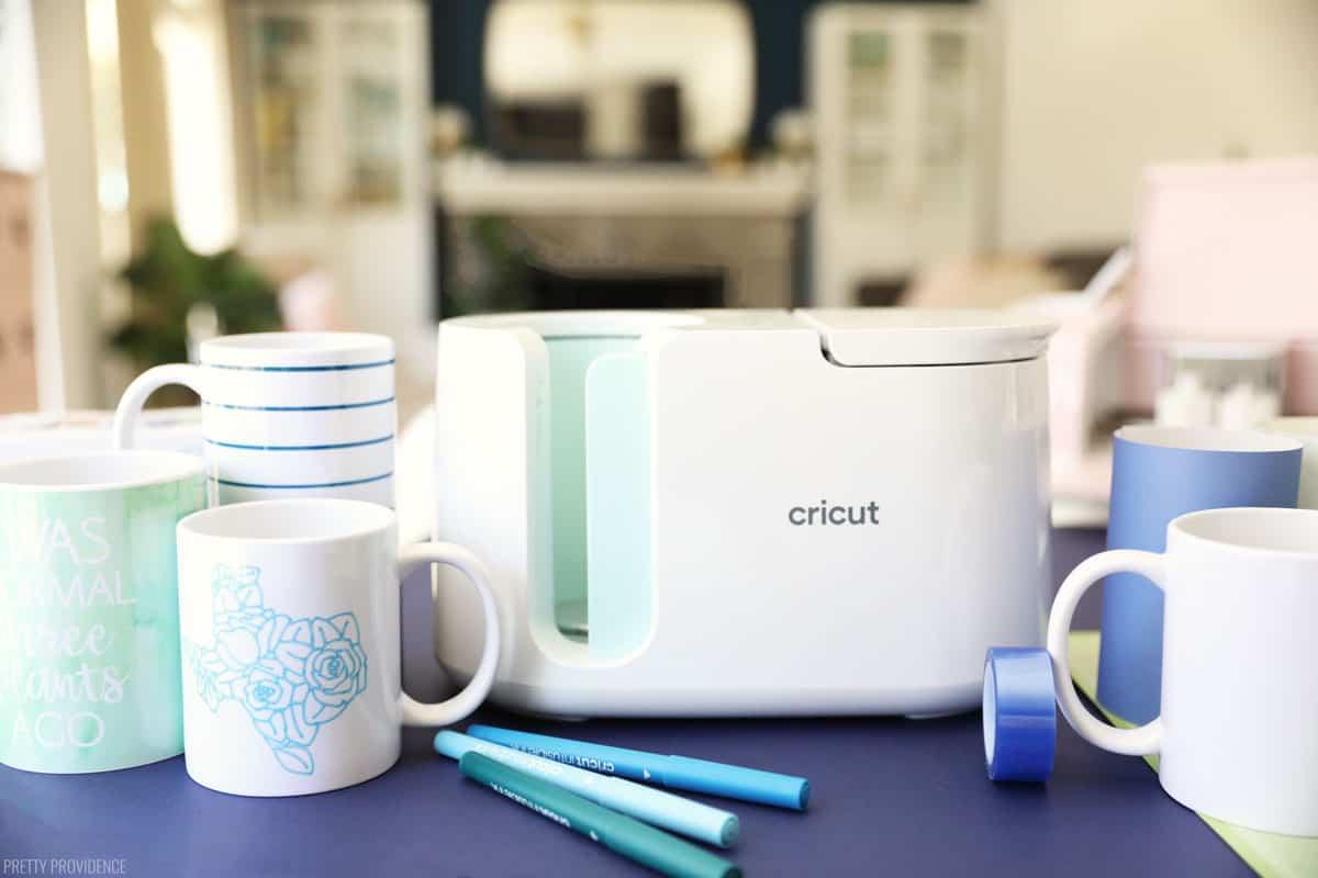 nouvelle presse de tasse Cricut sur vinyle bleu à côté de tasses et de fournitures