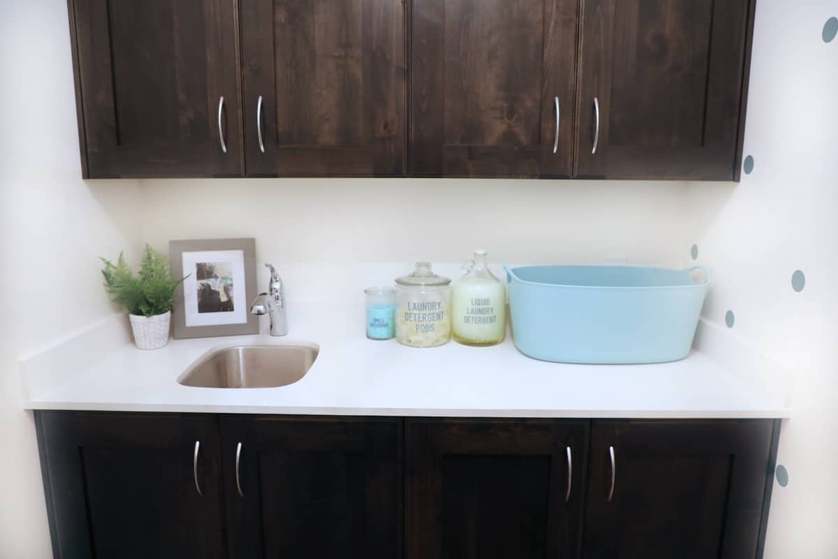small laundry room white counter with labeled jars