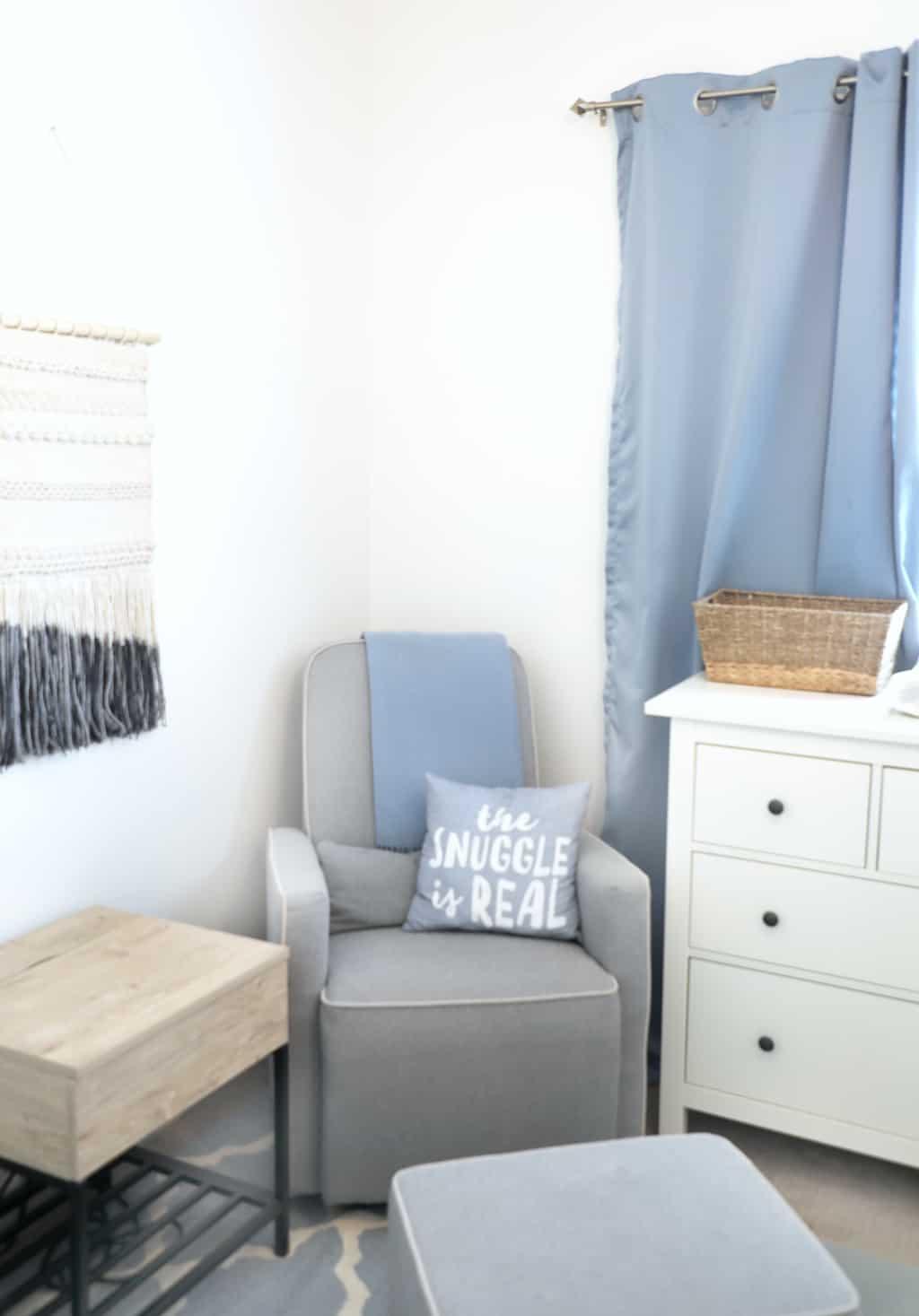 a cozy grey recliner in a corner of a nursery