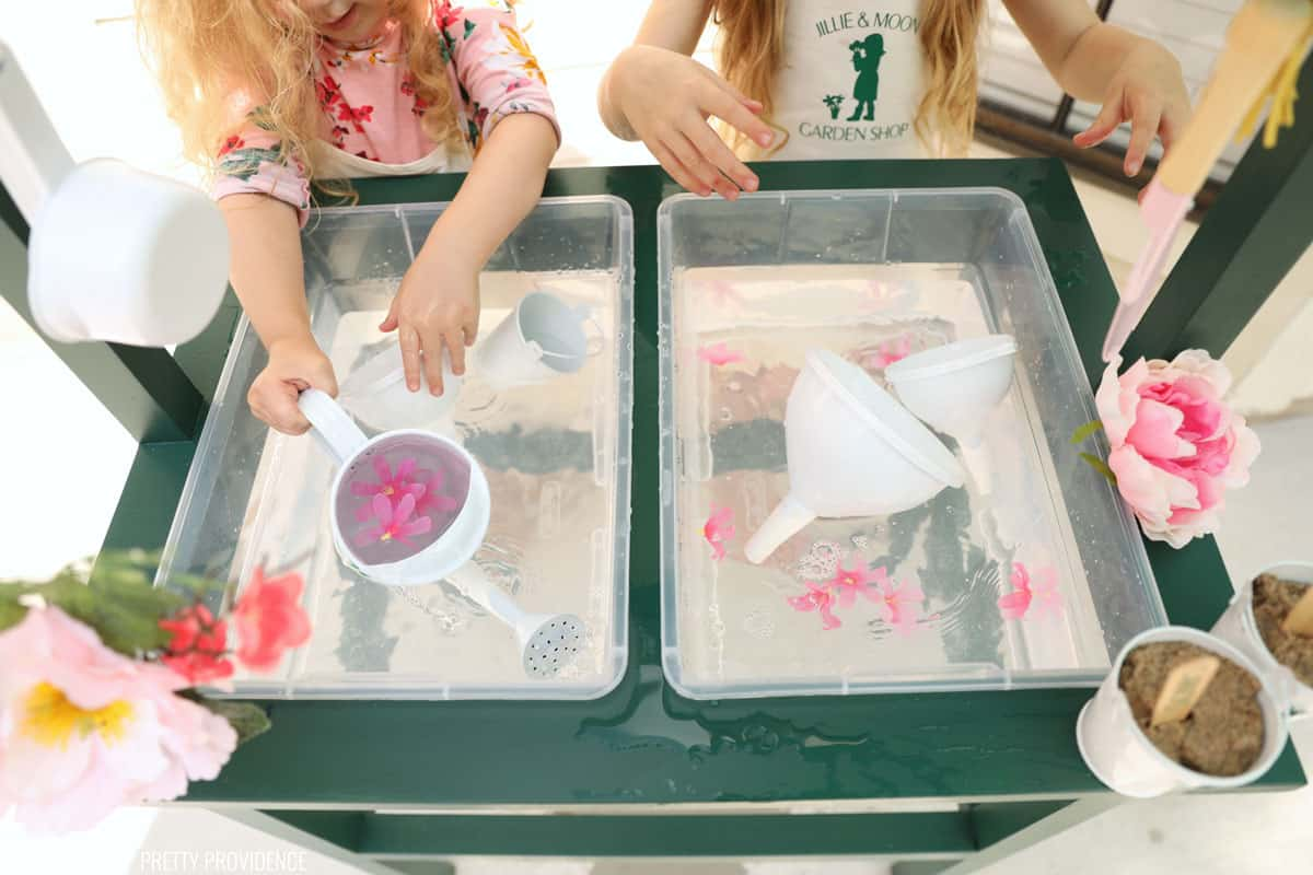 little hands pouring water and playing at a water table