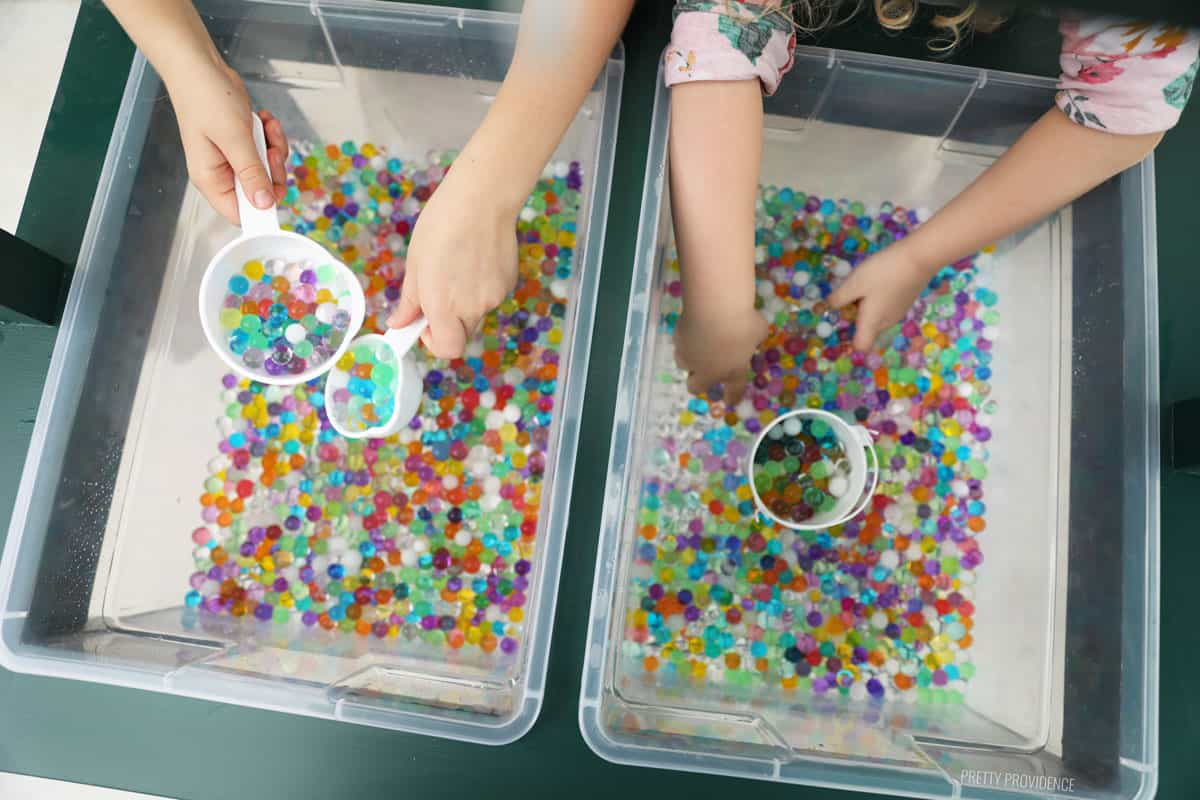 little hands playing with water beads in plastic bins