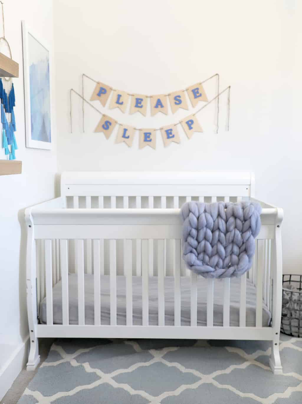 """white crib against a white wall with blue accents and a """"please sleep"""" banner"""