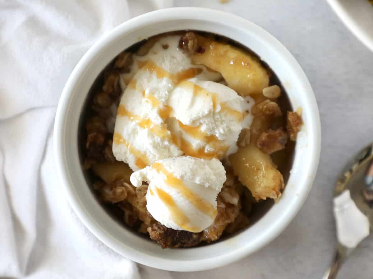 apple crisp with ice cream on top drizzled with caramel syrup