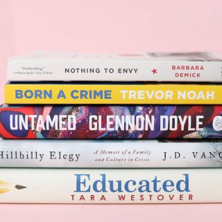 Stack of non-fiction books on a pink background, book club recommendations