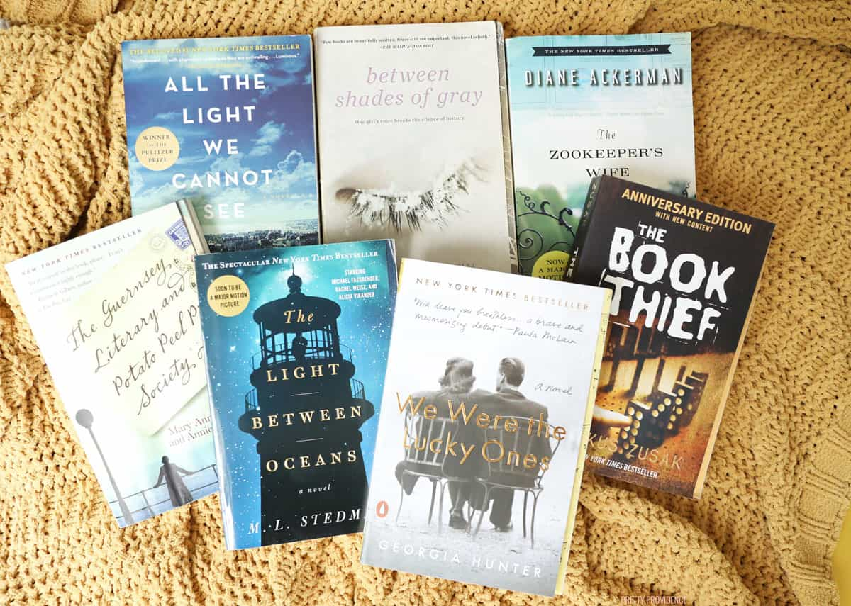 Seven paperback books, all historical fiction about WWII, on a yellow knit blanket