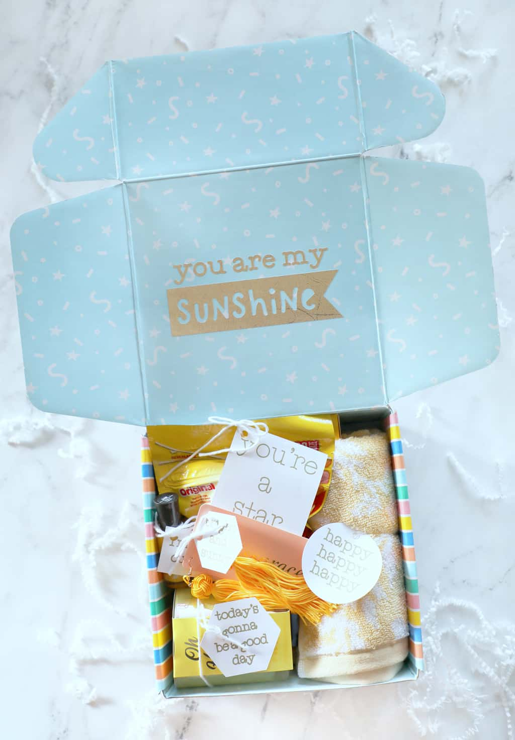 blue rainbow box that has bright yellow gifts inside with cute custom tags