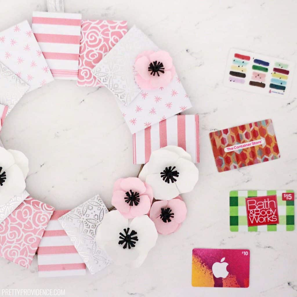 Wreath made with paper envelopes and paper flowers, with gift cards on the side
