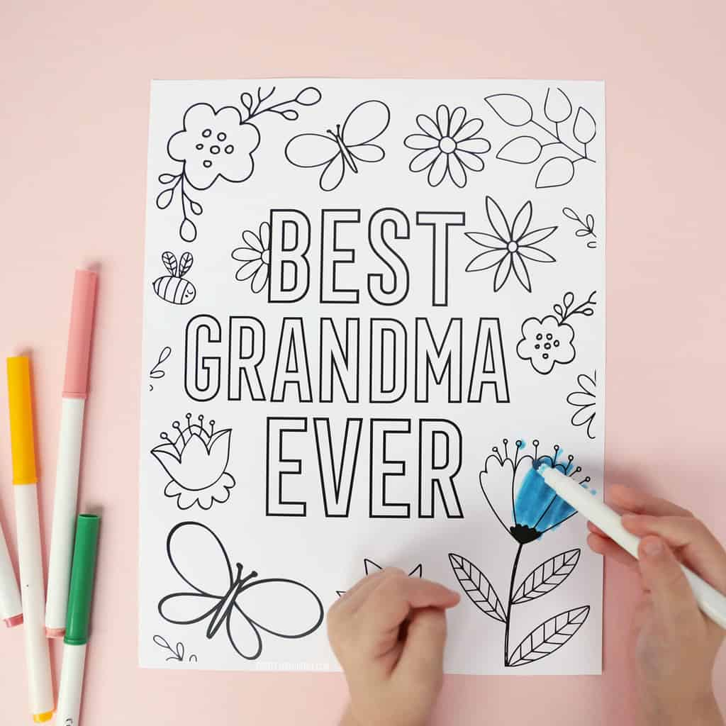 Little hands coloring a floral 'Best Grandma Ever' coloring page