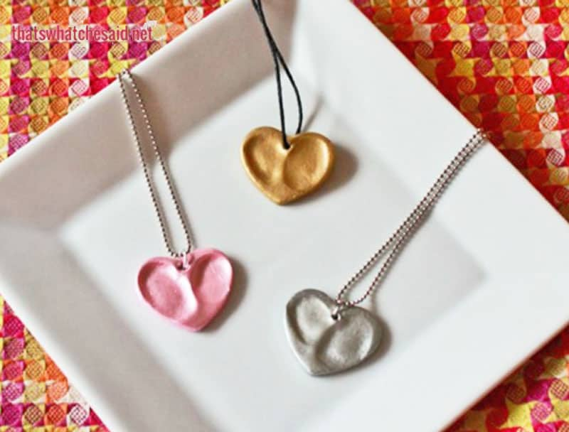 three DIY heart shaped clay thumbprint necklaces on a white plate