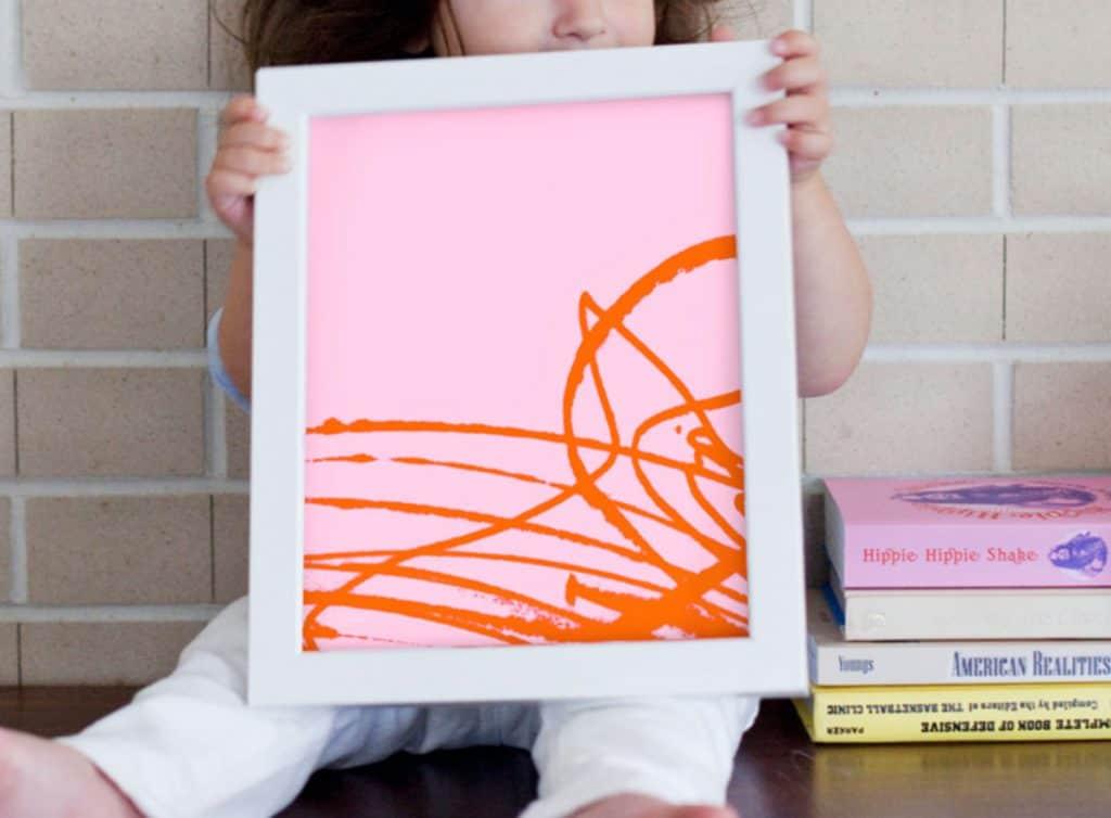 Small kid holding white framed modern art - kid scribbles turned into Modern