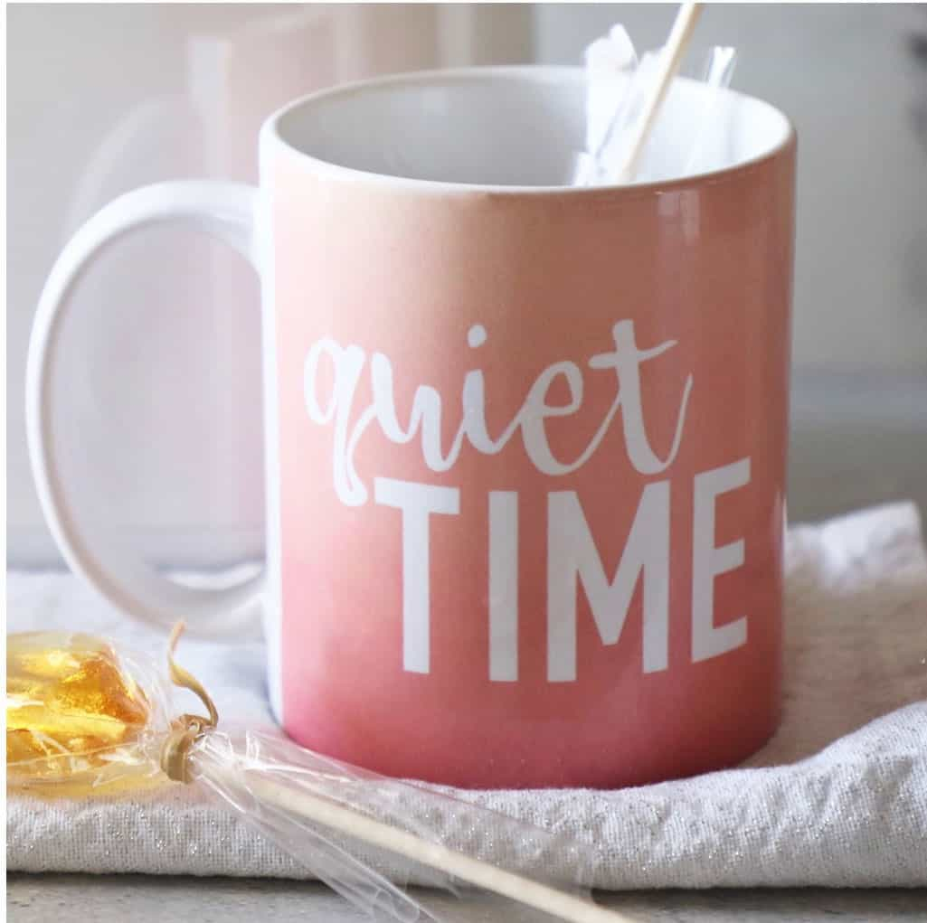 Pink sunset mug that says 'quiet time' on a white tea towel with stirring spoon