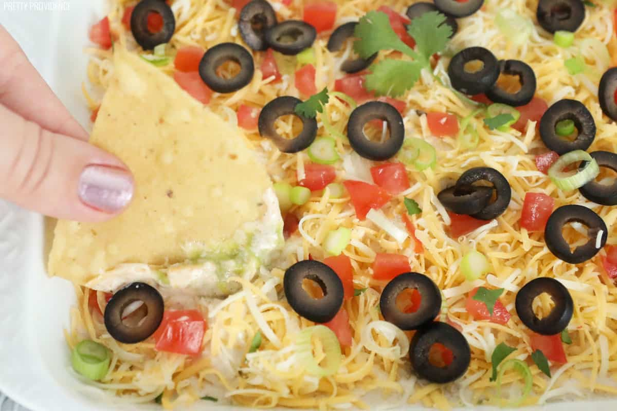 Seven layer bean dip with a tortilla chip being dipped into it.