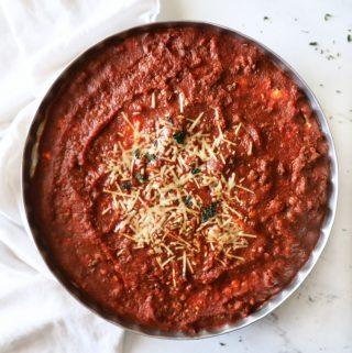 a spaghetti pie in a silver pie tin on a white quartz countertop
