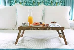 Breakfast in Bed tray with vinyl decal that says 'breakfast is served' on a bed