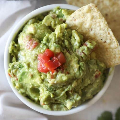 close up of chip in a guacamole bowl