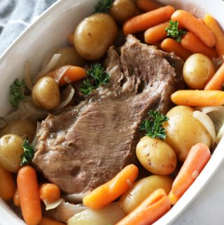 slow cooker pot roast in a white dish